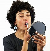 picture of ordinary woman  - Young woman is holding a mirror and putting lipstick on - JPG