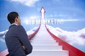 The word web marketing and unsmiling asian businessman with arms crossed against red steps arrow pointing up against sky