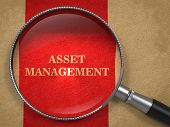 Asset Management. Magnifying Glass on Old Paper.