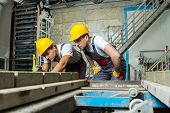 image of heavy equipment operator  - Worker and foreman in a safety hats performing quality check on a factory - JPG