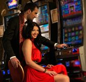 Beautiful young couple near slot machine in a casino