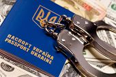 International Ukrainian passport with handcuffs on money background