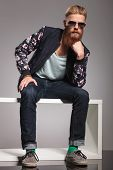 casual young man with a long red beard sitting like the thinker and looking into the camera. in a gr