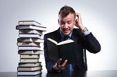 young business man reading a difficult book and scratching his head while sitting at his office. on
