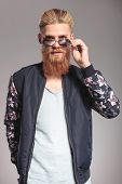 casual young man with a long red beard looking into the camera over his sunglasses while holding a h