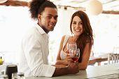 Young Couple Enjoying Drink At Outdoor Bar