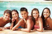 Portrait Of Teenage Friends Having Fun In Swimming Pool