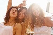 Three Teenage Girls Dancing And Taking Selfie