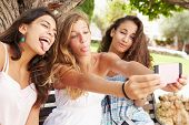 Three Teenage Girls Sitting On Bench Taking Selfie In Park