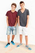 Portrait Of Two Hispanic Teenage Boys Leaning Against Wall