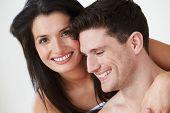 Romantic Couple Embracing Against White Studio Background