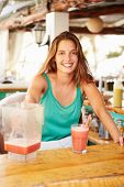 Woman In Restaurant Making Fruit Smoothies