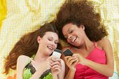 Two Female Friends Lying On Bed Using Mobile Phones