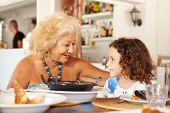 Grandmother And Granddaughter Enjoying Meal In Restaurant