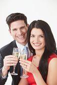 Studio Portrait Of Couple Celebrating With Champagne