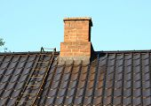 Brick Chimney On Black Roof With Metal Ladder