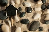 Close-up Of Stones And House Sticking Out Of The Sand In The Sunlight