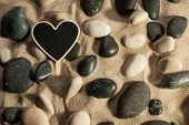 Close-up Of Stones And Heart Sticking Out Of The Sand In The Sunlight