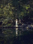 Photo of beautiful lady by pond in park. Reflection in water