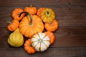 High angle shot of a pile of decorative pumpkins and gourds on a rustic dark wood table. Horizontal format with copy space.
