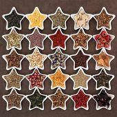 Large herb tea selection in star shaped porcelain bowls over lokta paper background.