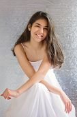 foto of cross-dress  - Beautiful biracial teen girl in white dress sitting arms crossed at knees - JPG