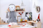 Happy young woman showing clock in christmas decorated kitchen