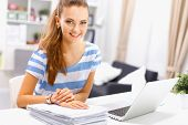 indoor picture of smiling woman with documents