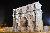 Triumphal Arch of Constantine nearby Colosseum in Rome by night, Italy