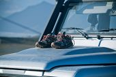 Trekking Shoes Are Drying On A Dirty 4Wd Car Bonnet