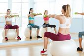 Women Exercising With Dumbbells.