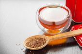 Rooibos In Spoon Closeup, Two Tea Cups And Tea Tin Box On Table