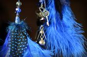 Blue dream catcher hanging on dark background with suspension key and heart