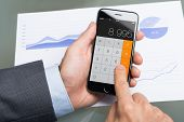 Businessman Using Calculator On Apple Iphone 6 At Table