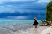 picture of dancing rain  - Beautiful Young Woman Dancing On The Beach With A Tropical Storm Coming - JPG