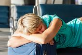 stock photo of sleeping bag  - beautiful young woman with blond short hair with a suitcase sleep on a chair at the airport and waiting for her flight - JPG