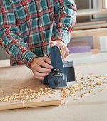Midsection of carpenter working with electric planer on wooden plank at workbench