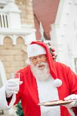 Portrait of Santa Claus with cookies and milk outside house