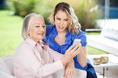 Granddaughter assisting senior woman in using smartphone at nursing home porch