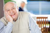Portrait of smiling senior man sitting at nursing home with grandson in background