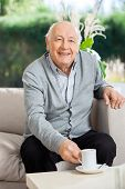 Portrait of happy senior man having coffee while sitting on couch at nursing home porch
