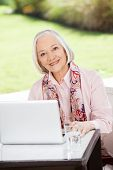 Portrait of happy senior woman sitting with laptop at table on nursing home porch