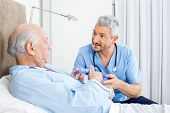 Male caretaker explaining prescription to senior man in bedroom at nursing home