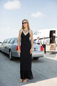 Full length of beautiful woman in elegant dress standing against limousine and private