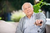 Portrait of senior man holding metal cane at nursing home porch
