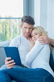 Middle Age Sweet Couple Watching Something on Blue Tablet in Their Sweet Moments.