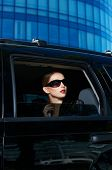 Serious Pretty Woman in Shades Inside Expensive Black Car. Isolated on Huge Building Background.