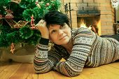 Woman Lying On Wooden Floor Near Fireplace With Christmas Fir-tree