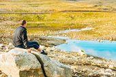 Man Sitting On Stone In Norwegian Mountains
