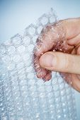 Man holding a piece of bubble wrap in his hand.